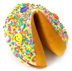 White Chocolate covered giant fortune cookie decorated with colorful stars and fun smiley faces